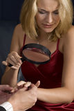 Skeptical fiance. Blond woman inspecting diamond size with magnifying glass prior to accepting proposal Stock Photo