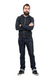 Skeptical hipster in black hooded sweatshirt with crossed arms looking at camera Stock Images
