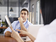 Skeptical interviewer looking at interviewee. A caucasian male interviewer looking skeptical while listening to an asian female interviewee Royalty Free Stock Photos