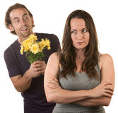 Skeptical Lady with Smiling Man. Skeptical female with smiling young men holding flowers royalty free stock image
