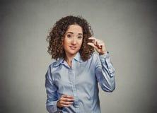 Skeptical młoda kobieta pokazuje małą ilość gesta z ręką dotyka Fotografia Royalty Free