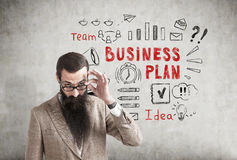 Skeptical man and business plan icons on concrete Royalty Free Stock Photo