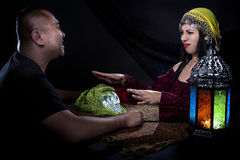 Skeptical Man with Con Artist Fortune Teller. Skeptical men arguing with a female con artist fortune teller or spirit medium about fraud Royalty Free Stock Photos