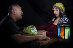 Skeptical Man with Con Artist Fortune Teller. Skeptical men arguing with a female con artist fortune teller or spirit medium about fraud Royalty Free Stock Photography