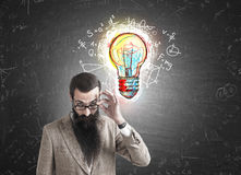 Skeptical man and light bulb with formulas Stock Images
