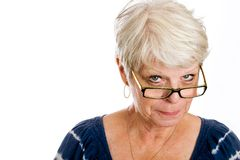 Skeptical mature woman. A gray haired, elderly woman with a skeptical expression on her face as she peers over the rim of her glasses Stock Photo