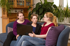 Skeptical mother with daughters and laptop Stock Photo