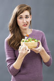 Skeptical 20s girl questioning the taste of a mixed green salad Stock Image