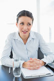 Skeptical stylish brunette businesswoman joining her hands and looking away Royalty Free Stock Image