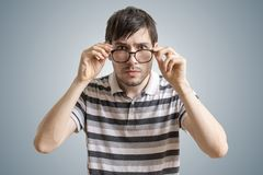 Skeptical or suspicious man is looking at you and touching glasses Stock Photo