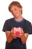 Skeptical teenager with piggy bank Stock Photo