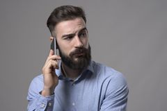 Skeptical uncertain bearded business man talking on the mobile phone looking back over the shoulder at copyspace Stock Photography