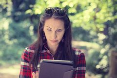Skeptical unhappy serious woman using mobile pad computer outdoors Stock Photo