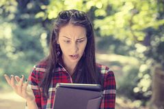 Skeptical unhappy serious woman using mobile pad computer outdoors Royalty Free Stock Image