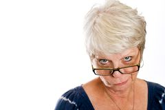 Skeptical woman. Mature, white haired woman with a skeptical look on her face while looking over her glasses Stock Photography