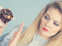 Skeptical woman holding chocolate cupcake muffin. Skeptical woman holding muffin cupcake with dark chocolate flavour having disgusted face expression being on Royalty Free Stock Images