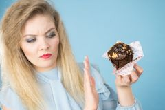 Skeptical woman holding chocolate cupcake muffin royalty free stock photography