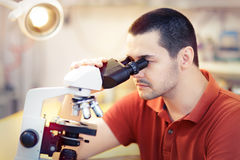 Skeptical Young Male Researcher with microscope Stock Photo
