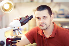 Skeptical Young Male Researcher with microscope Stock Image
