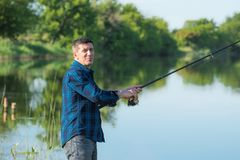 Skeptically smiling hobby fisherman with rod. Royalty Free Stock Photo