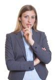 Skeptische blonde Geschäftsfrau in einem grauen Blazer Lizenzfreie Stockfotografie