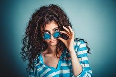 Skeptische Frau, die nach unten Sonnenbrille skeptisch hält lizenzfreie stockfotografie