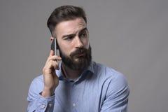 Skeptischer unsicherer bärtiger Geschäftsmann, der am Handy zurück betrachtet über der Schulter copyspace spricht Stockfotografie
