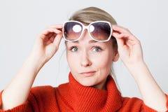 Skeptisk blond flicka som tar bort hennes solglasögon för sol i vinter Royaltyfri Foto