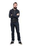 Skeptisk hipster i svart med huva tröja med korsade armar som ser kameran Arkivbilder