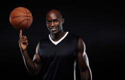 Säker basketspelare som balanserar bollen på fingret Arkivbild