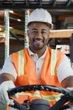 Säker industriarbetare som kör gaffeltrucken på arbetsplatsen Royaltyfri Bild