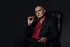 Säker stilig affärsman som i regeringsställning sitter stol och röker cigarren Arkivbild