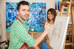 Sketch artist drawing a pretty model. Handsome male Hispanic artist drawing a sketch of a cute young women in his studio Royalty Free Stock Photography