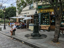 Sketch artist in front of Shakespeare and Company, Paris; cafe diners in background. Paris, France, summer 2016: Sketch artist sits in front of bookstore Royalty Free Stock Images