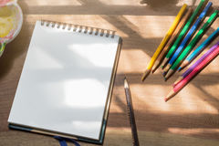 Sketch book with color pencils on wooden work desk. Background Royalty Free Stock Photo