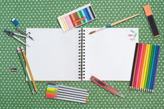 Sketch book and paint tools on table cloth Royalty Free Stock Photo