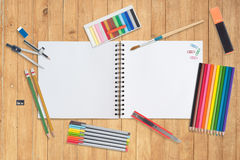 Sketch book and paint tools on wood background Royalty Free Stock Photo
