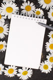 Sketch book and pen on a table decorated with flowers Royalty Free Stock Image
