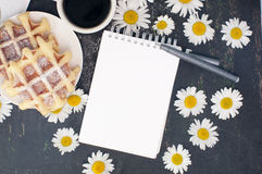 Sketch book, pen waffles and coffee on a table decorated with flowers. Mock up Royalty Free Stock Images