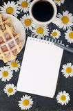 Sketch book, pen waffles and coffee on a table decorated with flowers. Mock up Stock Image