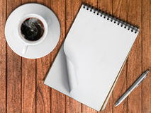 Sketch book Silver pen and White cup of hot coffee. On wood table Royalty Free Stock Images