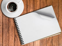 Sketch book and White cup of hot coffee. On wood table Stock Photo