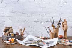 Sketch and cups with brushes. On wooden table in workshop Royalty Free Stock Photography