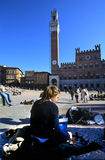 Sketch of the girl in Piazza del Campo. Scenic view of tourists on Piazzo del Campo with Torre del Magnia, Siena, Tuscany, Italy Royalty Free Stock Images