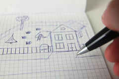 Sketch of house. Man sketching new house on paper stock photo