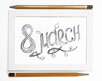 Sketch of inscription on March 8. Sketch of a pencil drawing inscription on March 8 on a white background in a white frame and two pencils Royalty Free Stock Photography