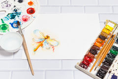 Sketch of Orange Dragonfly And Paints. Hand Drawn Sketch of Orange Dragonfly, with lying paints, paintbrushes and palette on the white brick background - concept royalty free stock photography