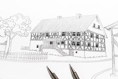 Sketch of a traditional timber framed home. Detailed hand drawn sketch of a timber framed home, traditional Siegerland house with small garden, fence and tree Stock Photo