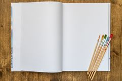 Sketchbook με τα πινέλα στον ξύλινο πίνακα στοκ εικόνες