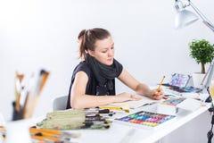 Молодой женский эскиз чертежа художника используя sketchbook с карандашем на ее рабочем месте в студии Портрет взгляда со стороны Стоковое Изображение RF